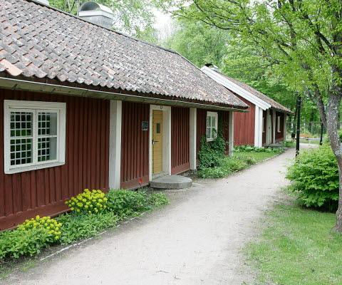 Två små gamla röda trähus med vita knutar på Turbinhusön.