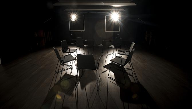 Ett svart rum med trägolv och svarta stolar i en ring med två starka strålkastare som lyser mot stolarna.
