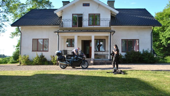 2 personer som står utanför Berglunda vandrarhem med en motorcykel.