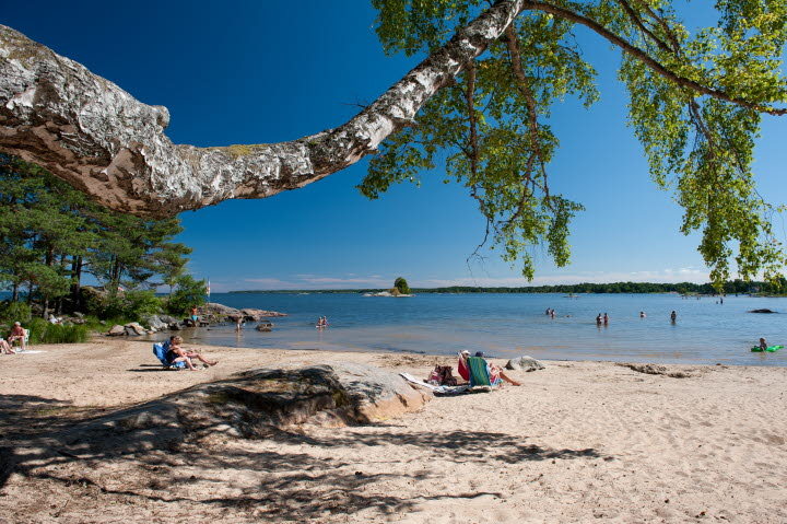 The sandy beach of Gardesanna by Lake Vänern, people sunbathing.