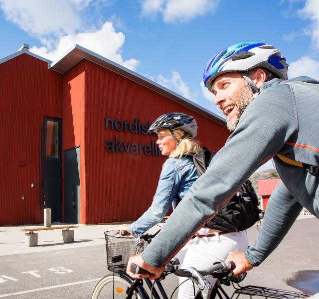 Två cyklister vid stort rött hus