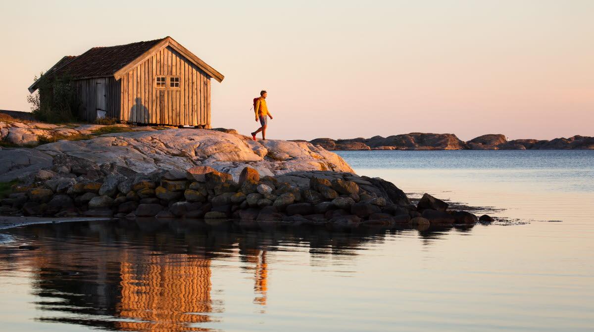 Vandrande man vid sjöbod i solnedgången