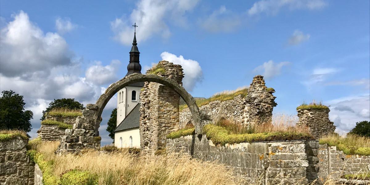 Gudhems klosterruin med Gudhems kyrka i bakgrunden.