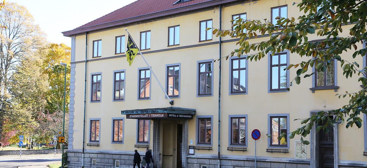 Vy över Stadshotellet i Tidaholm. Ett gult stort stenhus.