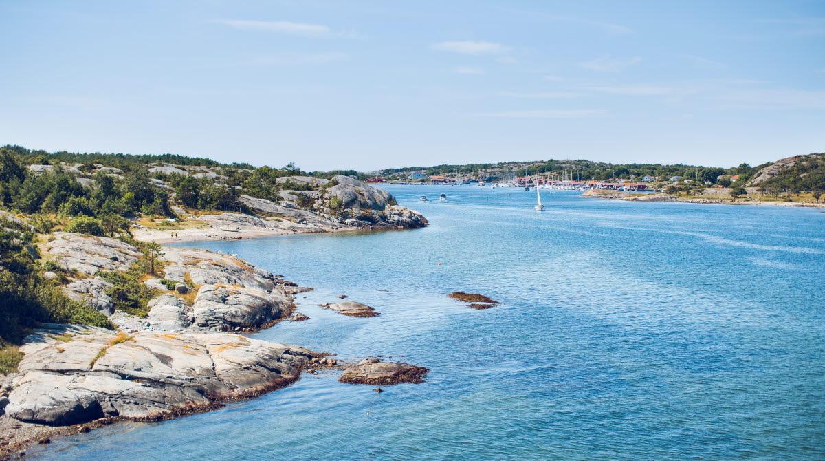 Solig vy över hav och klippor på kusten.