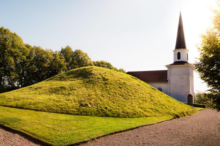 En bild på Kung Ranes hög med Flistad kyrkan i bakgrunden