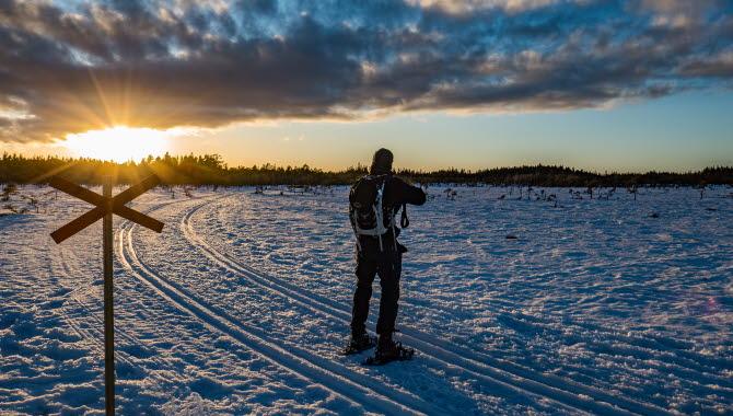 En man i snöskor står i solnedgången och blickar ut över ett snöklätt Blängsmossen.