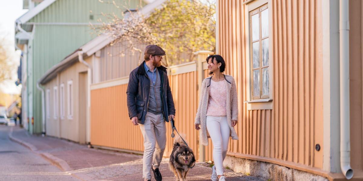 Ett par på vårpromenad med sin hund längs med Långgatan mitt i den gamla trästaden i Hjo.