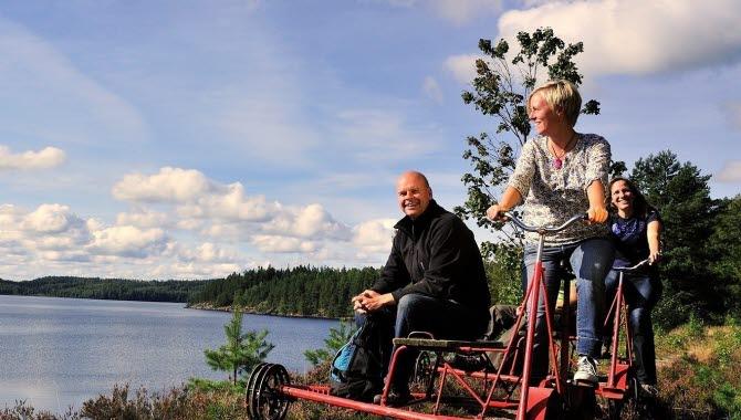 Tre personer som cyklar dressin utmed en sjö.