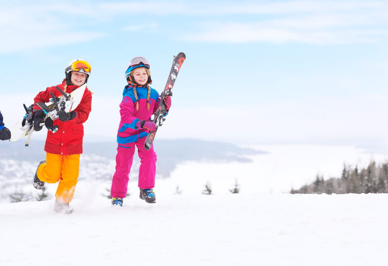 Three children in colorful clothes with skis in the arms running on top of Ulricehamn Ski Center.