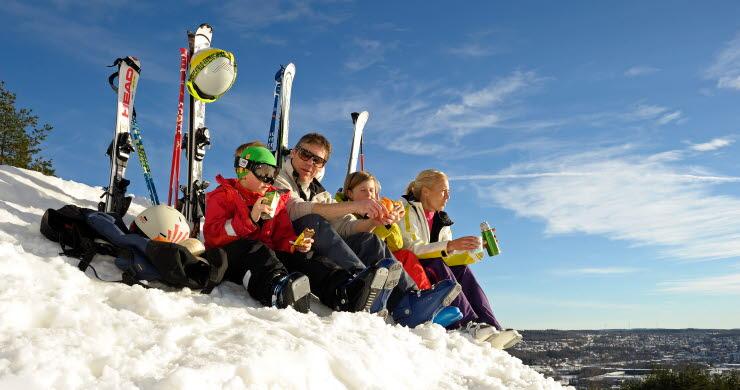 Familj sitter i snön med skidor uppställda bakom sig