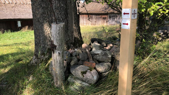 Stolpe i trä med pilgrimsmärket.