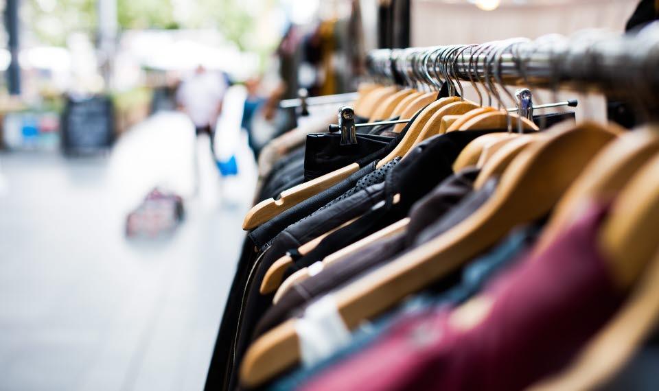 Kläder till försäljning som hänger på galgar utomhus .