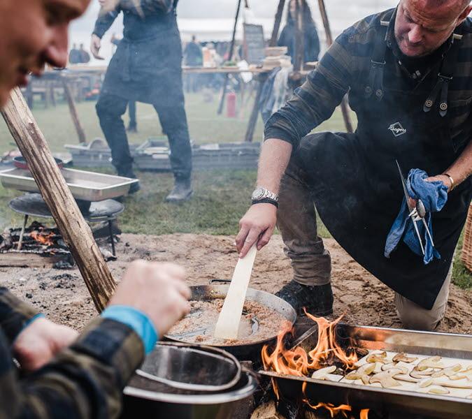 Två män i full färd med att laga mat över öppen eld under SM i utomhusmatlagning