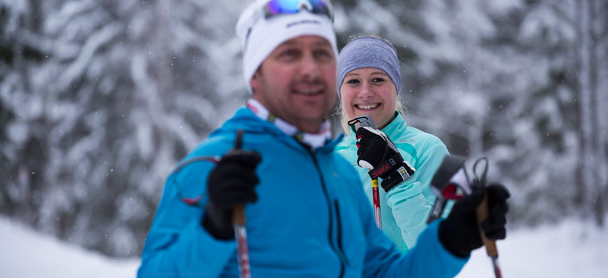A girl and guy dressed in cross-country ski equipment checking into the camera.