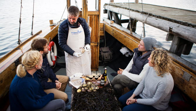 People tasting oysters on a boat