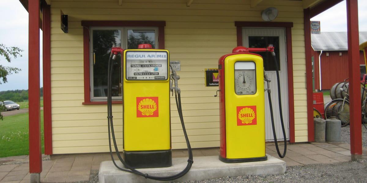 En gammal shellmack med två gula bensinpumpar framför.