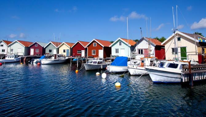 Färgglada sjöbodar med ankrade småbåtar vid bryggorna på Nordkoster.