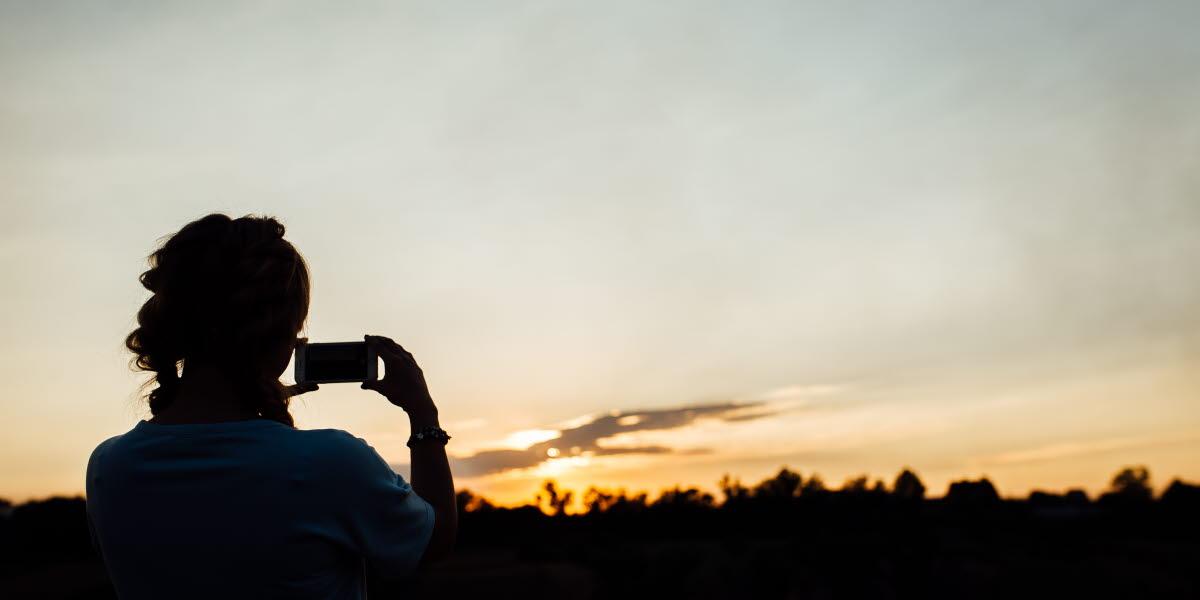 Kvinna som tar bild ute i naturen med sin mobil.