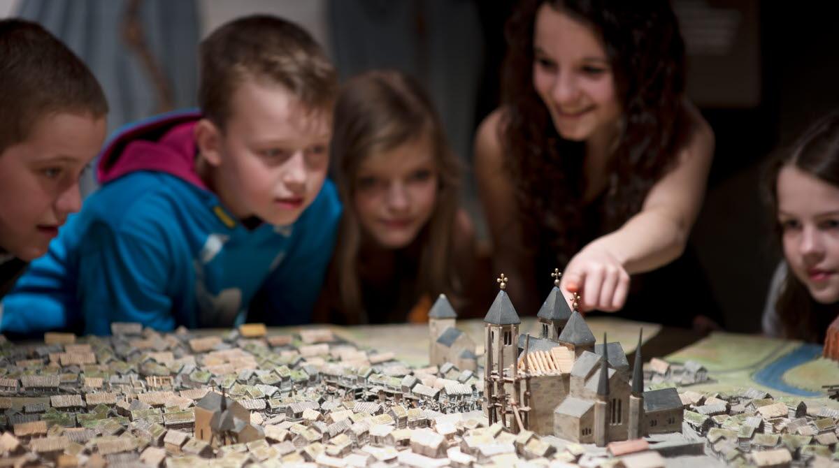 Barn tittar på modell av medeltiden i Skara på Västergötlands museum