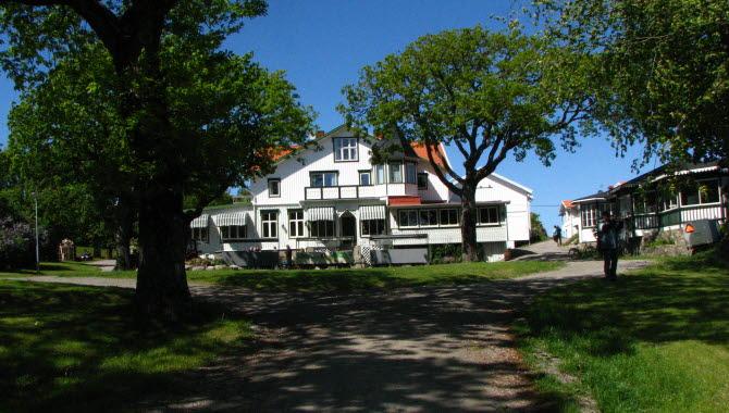 Hotel Koster Ekenäs, vit träbyggnad med grönvita markiser och högväxta ekar framför hotellet.
