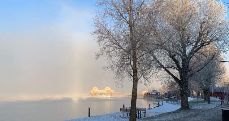 Kallbadhuset med blå himmel och vintriga träd i förgrunden