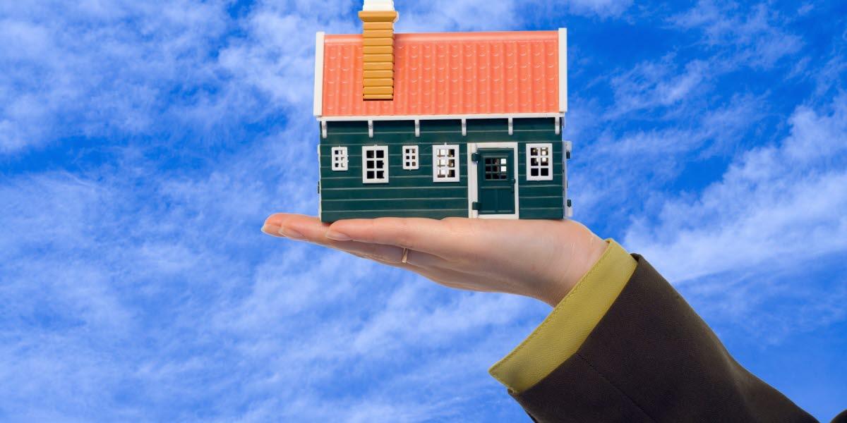 Ett litet miniatyr hus hålls upp i en hand med blå molnbeklädd himmel i bakgrunden.