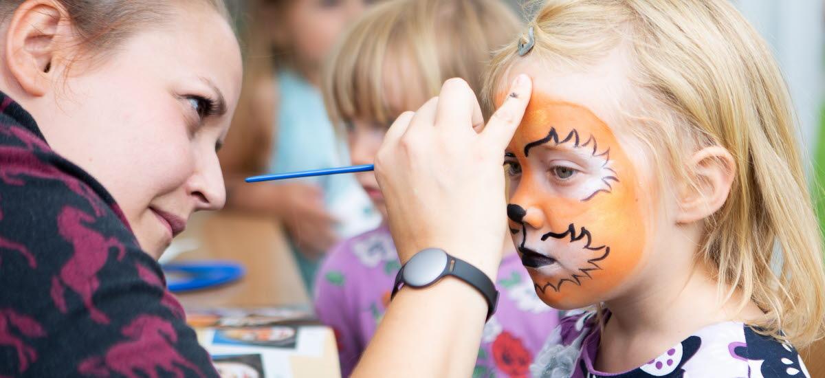En flicka blir ansiktsmålad av en kvinna till en tiger.