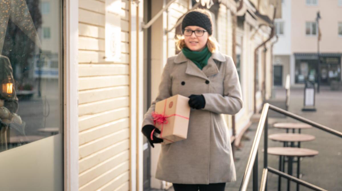 Kvinna med ett paket under armen.