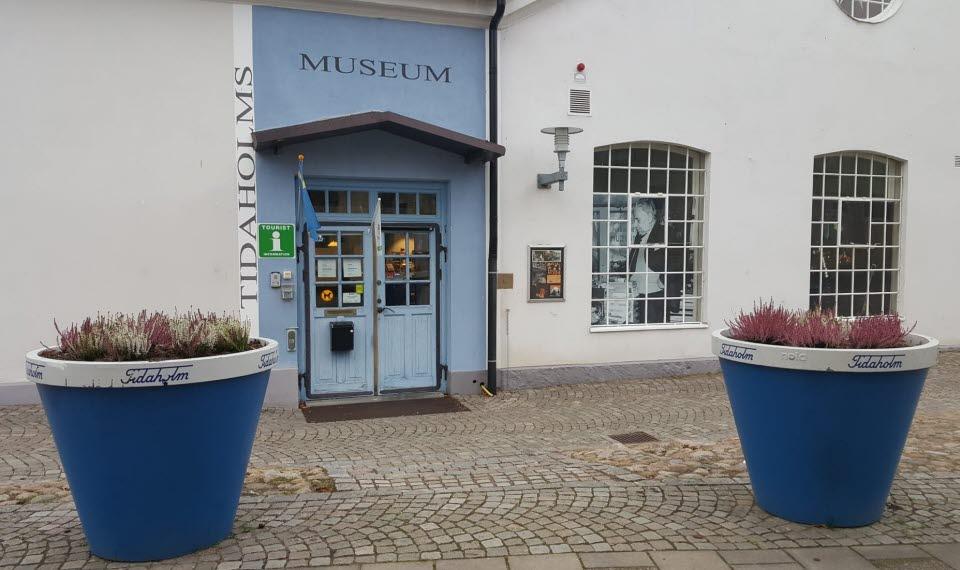 Museets blå entrédörr med två stora, spröjsade fönster till höger. Närmast står två stora mörkblå blomkrukor med ljung i.