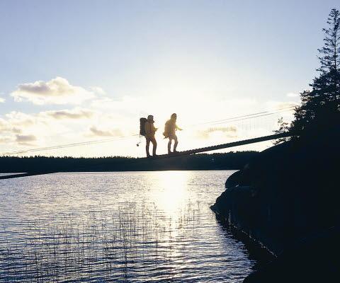 Två personer går över den smala hängbron vid färingesjön. Solen står lågt på himlen.