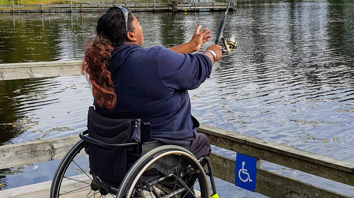 Kvinna som sitter i rullstol och fiskar vid Björnsjön på Hökensås.