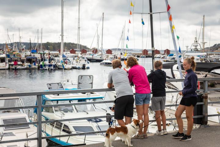 Familj står på strandpromenaden i centrala Strömstad och tittar ut över gästhamnen.
