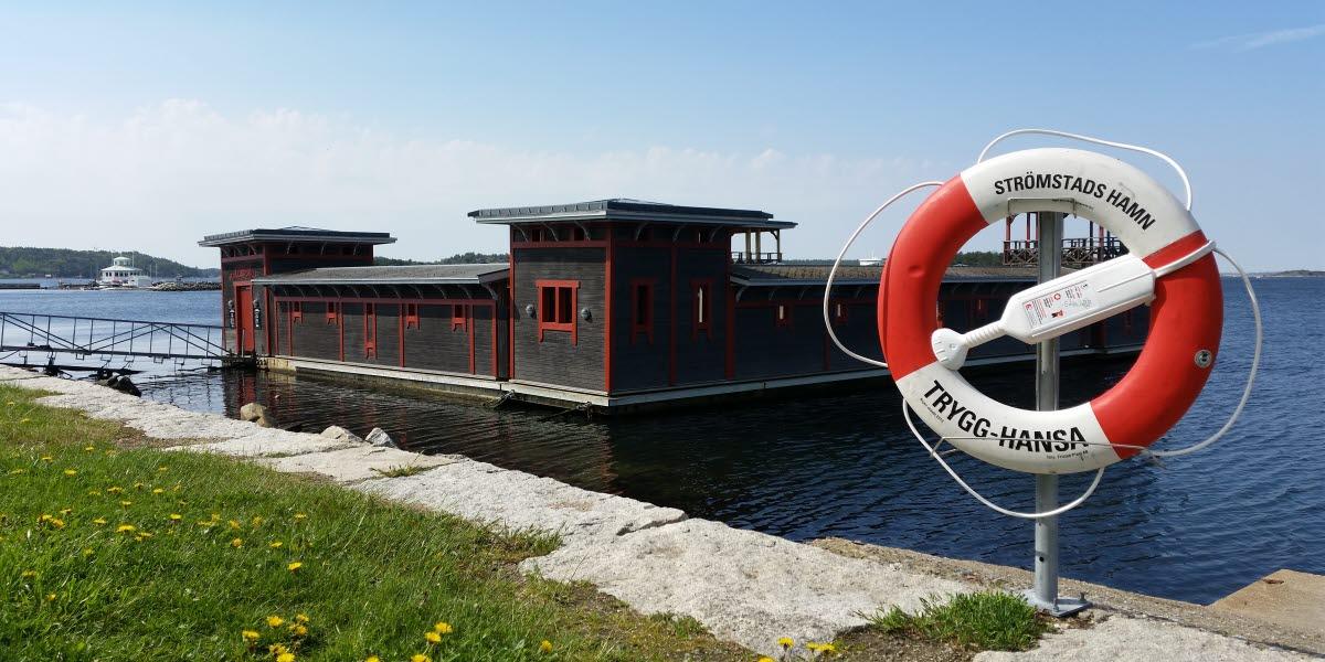 Kallbadhuset i Strömstads hamn en solig dag. I förgrunden syns en gräsplätt med maskrosor och en röd-vit livboj.