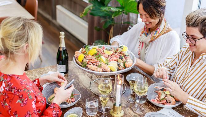Gäster njuter av en skaldjursplatå på Göstas Fiskekrog.