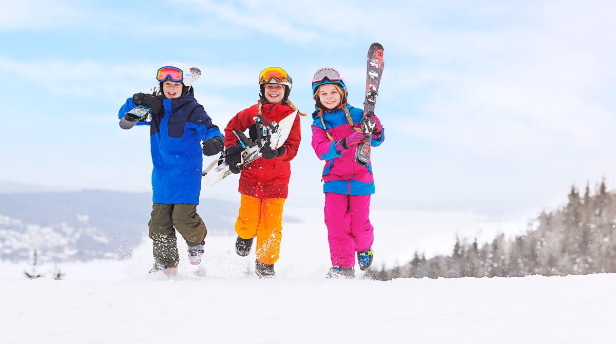 Barn i färgglaga skidkläder springer med skidor i händerna på Ulricehamn Ski Center