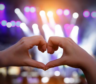Två händer som bildar ett hjärta på ett evenemang