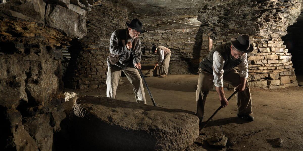 Tre äldre män som står och gräver i  Qvarstensgruvan.
