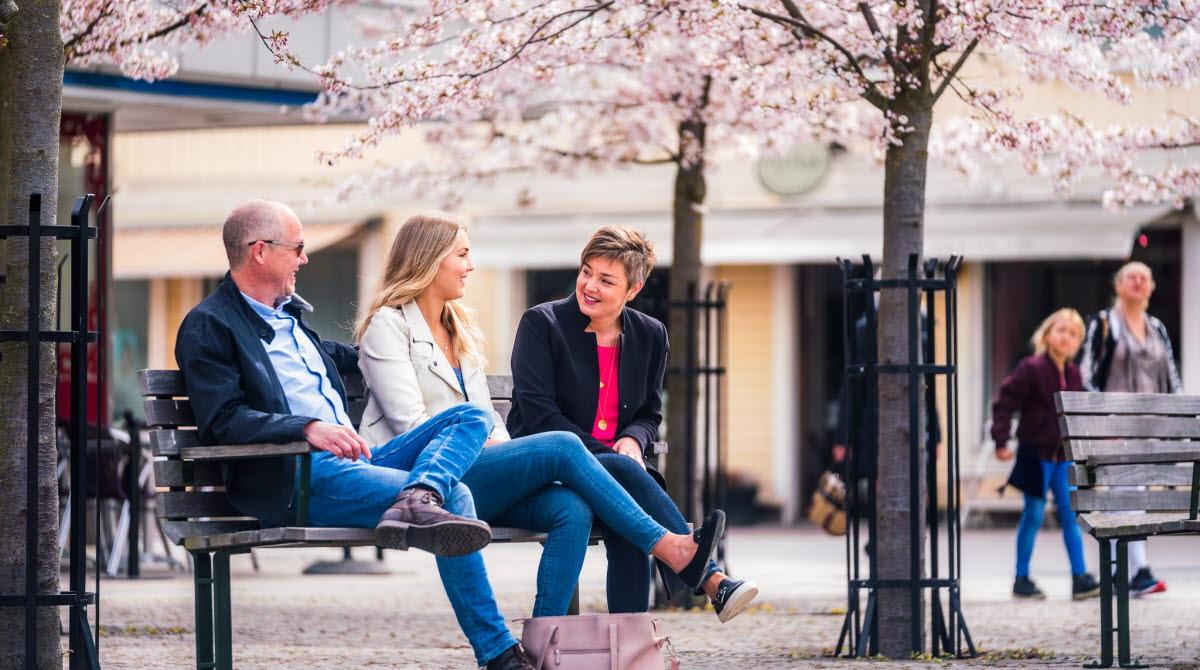 Familj sitter på bänk vid torget i Hjo, på våren.
