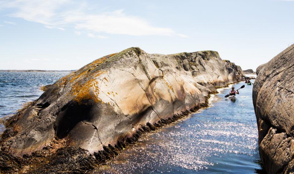 En person i kajak paddlar igenom en smal kanal mellan två klippor vid Kosteröarna.