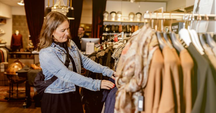 Kvinna som kikar på kläder i en butik.