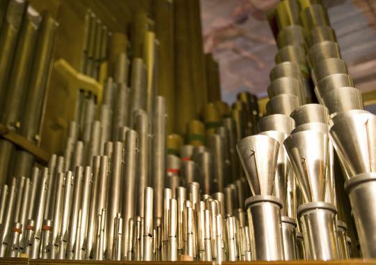 Närbild på guldfärgade orgelpipor.