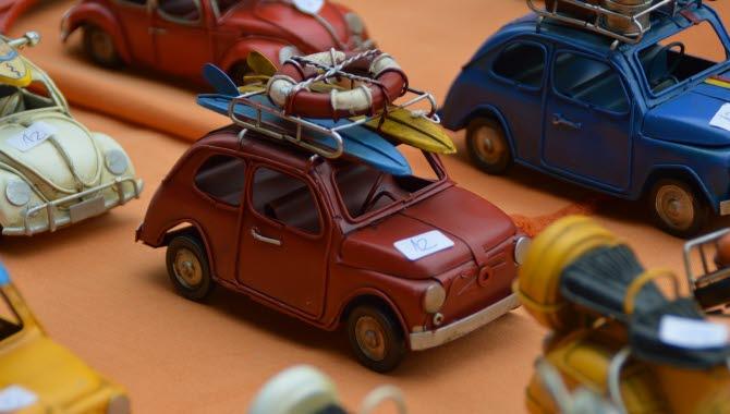Små färgglada leksaksbilar av äldre modell står uppradade och har små klisterlappar på motorhuven med siffrorna 12 på.