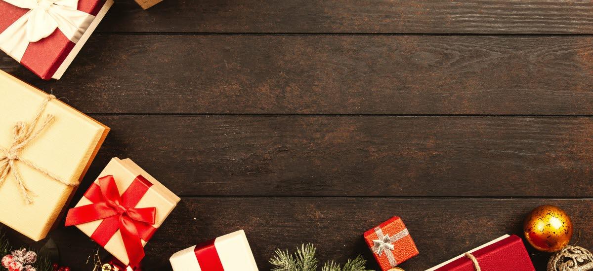 Flera julklappar som ligger på ett bord av trä