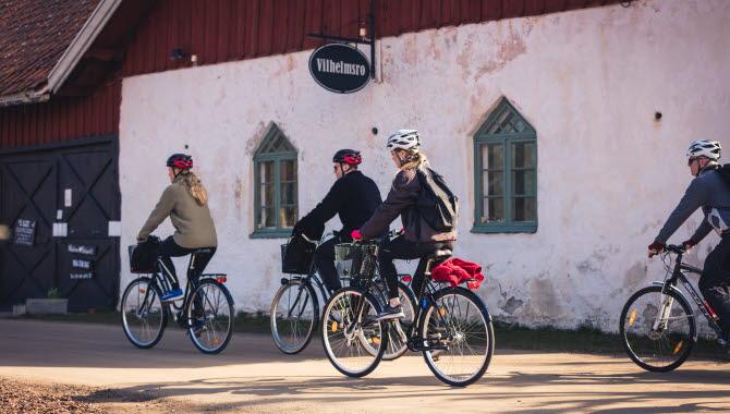 Fyra personer som cyklar förbi en ladugårdsbyggnad med en skylt Vilhelmsro på väggen.