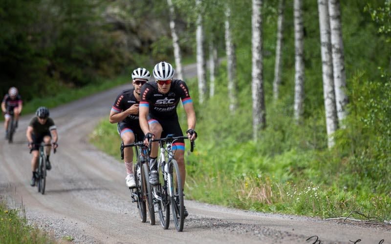 4 guys riding bikes on gravel road