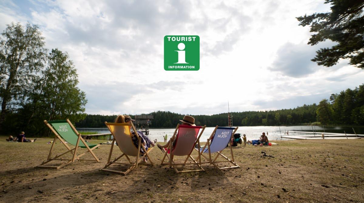 Vy över Lilla Havssjön med fyra solstolar och logotype för turistbyrån.