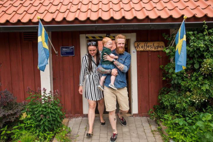 En man som håller ett barn i famnen och en kvinna går ut ur Kaffestugan på Turbinhusön i Tidaholm en sommardag.
