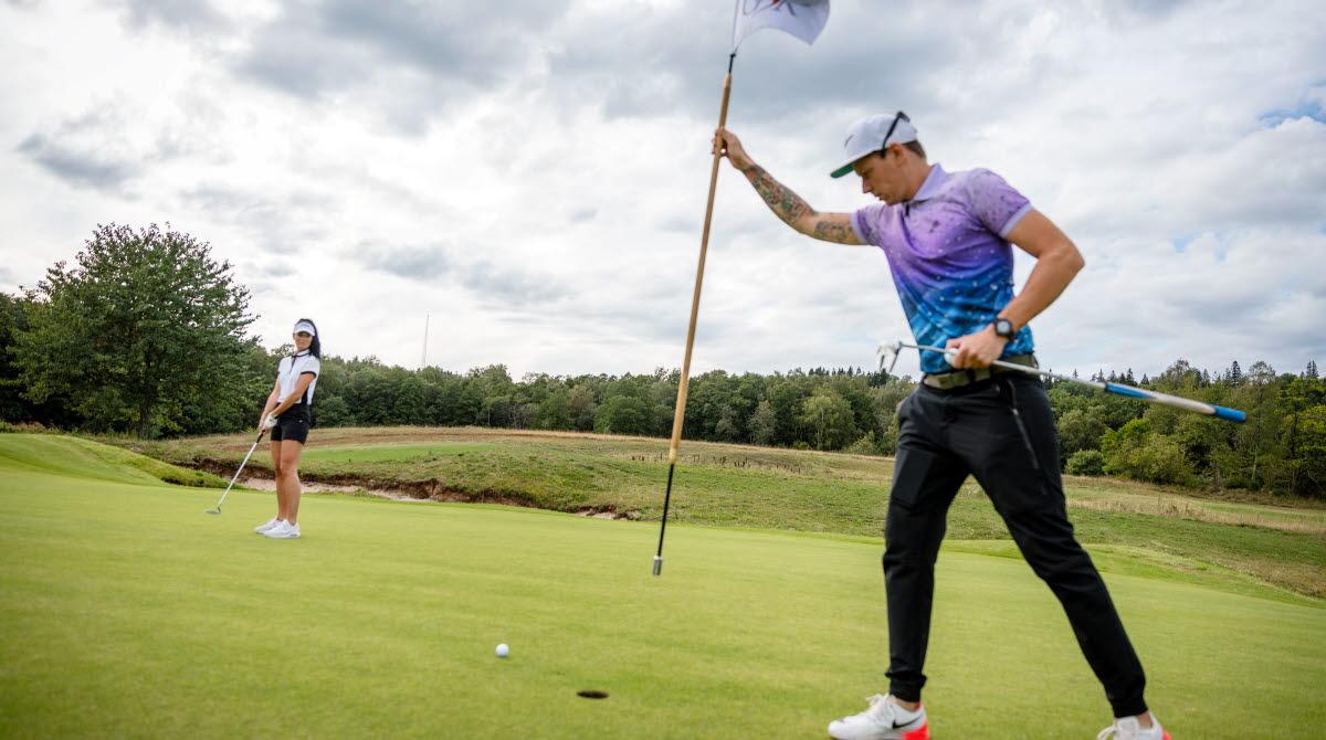 Två personer som golfar, killen i förgrunden håller i en golf flagga, tjejen i bakgrunden gör sig redo att slå