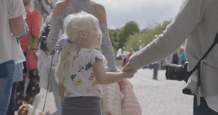 Flicka håller sin mamma i hand och tittar upp mot henne medan de går längs gatorna i Alingsås